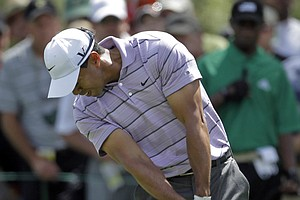 Tiger Woods hits a shot at the first hole Saturday.