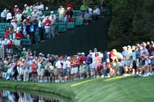 Phil Mickelson looks on from the 16th green in front of a gallery of fans.
