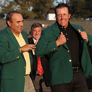 Angel Cabrera of Argentina presents Phil Mickelson with the green jacket. Mickelson won his third Masters.