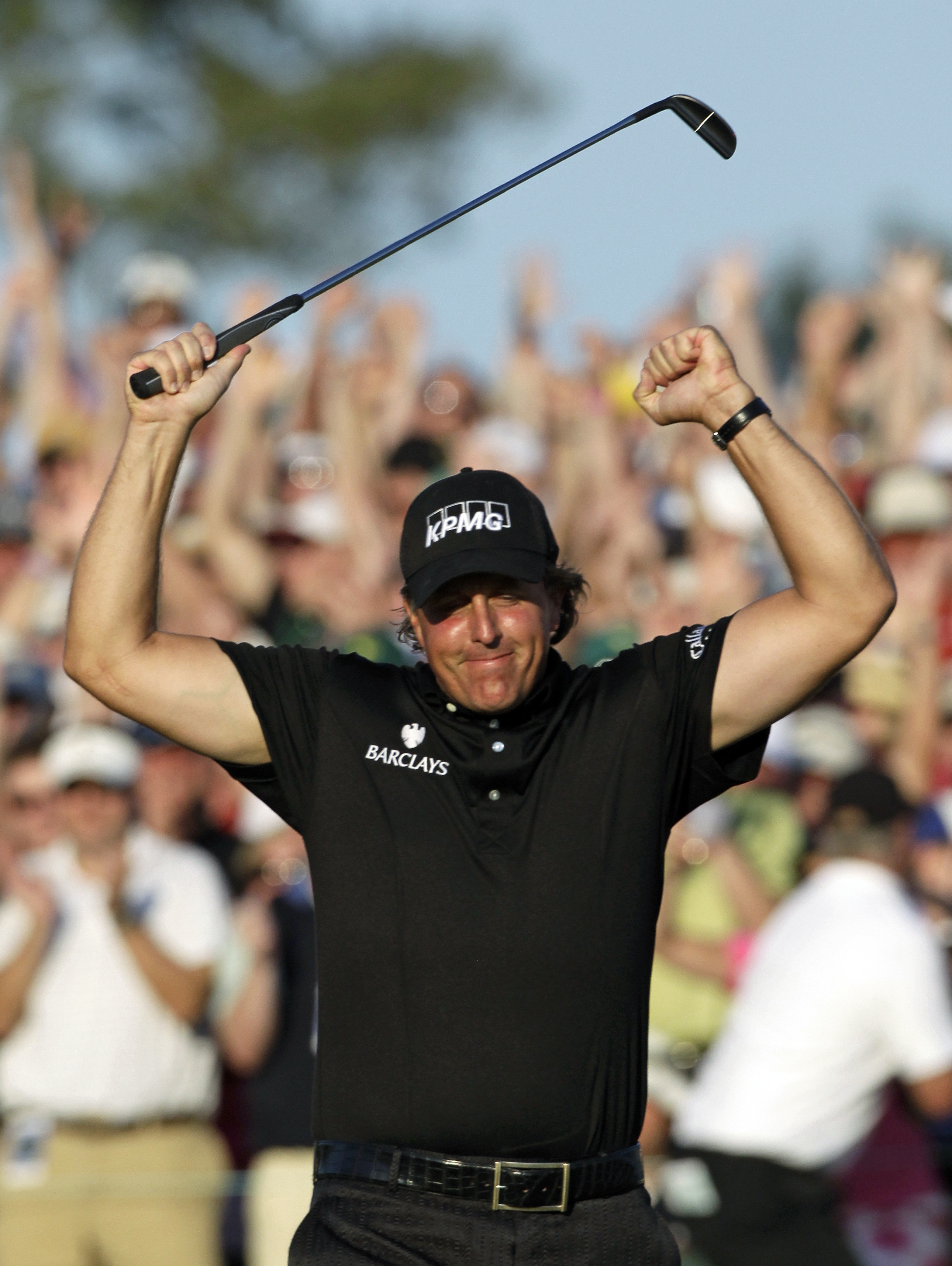 Phil Mickelson celebrates on the 18th green after winning the Masters.