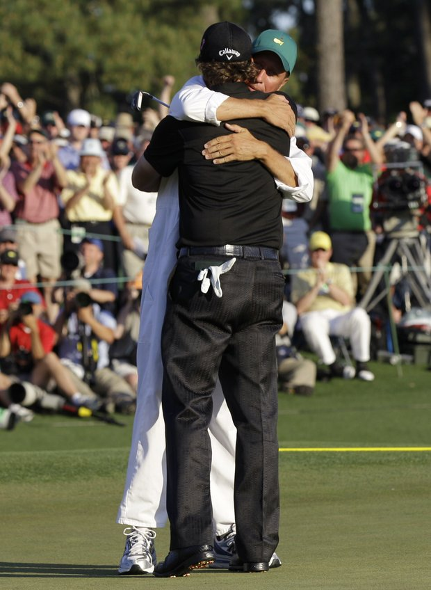 Phil Mickelson hugs his caddie, Jim Mackay, after winning the Masters.