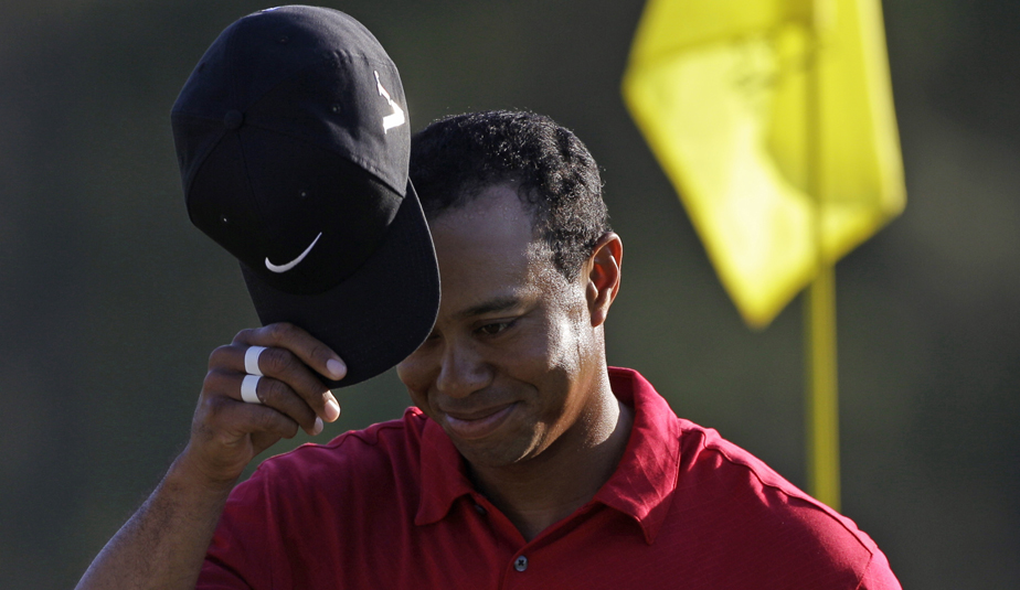 Tiger Woods tips his cap while walking off the 18th green Sunday.