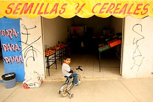 A yound boy stis on his bicycle outside a local shop on the streets near the education center of La Barranca in Guadalajara.