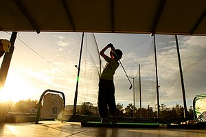 A young boy hits balls during the Ochoa Golf Academy in Guadalajara, Mexico, as the sun begins to set.