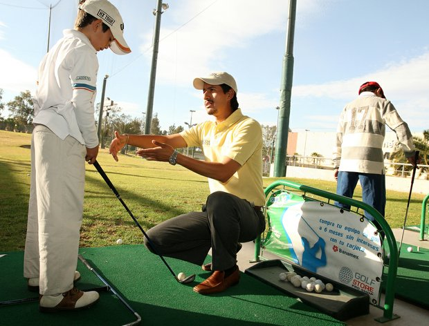 Alejandro Delgado works with student Alan Alonso Ascencio, 10, at Lorena Ochoa's Golf Academy in Guadalajara, Mexico.