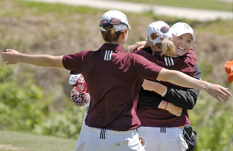 Texas A&M junior Sarah Zwartynski is hugged by her teammates after sinking the putt to win the Big 12 Championship.