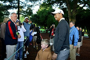 During the pro-am of the Quail Hollow Championship in Charlotte in May, Tiger Woods stops on his way to the second hole to pose with Andrew Nicholson, 6, of Gastonia, N.C. (April 28, 2010)