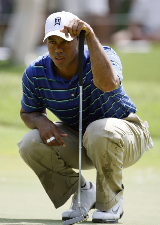 Tiger Woods lines up a putt Thursday at TPC Sawgrass.