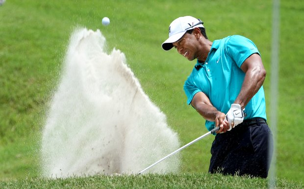 Tiger Woods blasts out of a greenside bunker at No. 9. He made par.