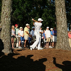 Dustin Johnson hits a shot out of the trees at No. 10. Johnson shot a pair of 71s to make the cut.