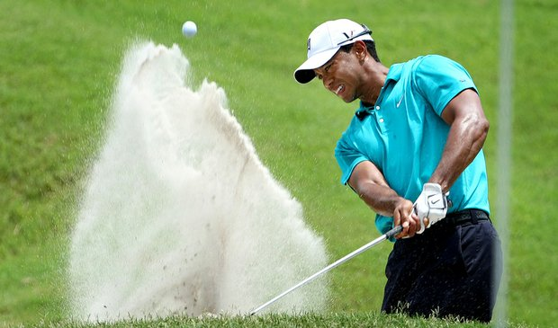 Tiger Woods blasts out of a bunker near the ninth green during the second round of The Players.