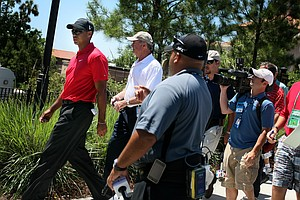 Tiger Woods is surrounded by the media and PGA Tour officials after withdrawing from the final round.