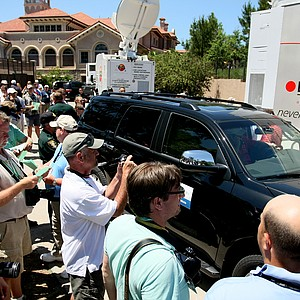 Photographers and reporters with several media outlets wait for Tiger Woods to exit the fitness trailer after withdrawing on Sunday.