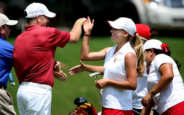 USC's director of golf, Kurt Schuette (left) high-fives Belen Mozo after her second-round 72.