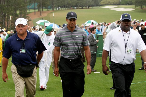 Tiger Woods walks with security during the first round of the 2010 Masters.