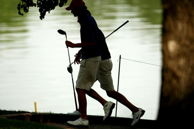Florida State's Wesley Graham and Clemson's Luke Hopkins are silhouetted as they walk to the 17th tee during Round 2.