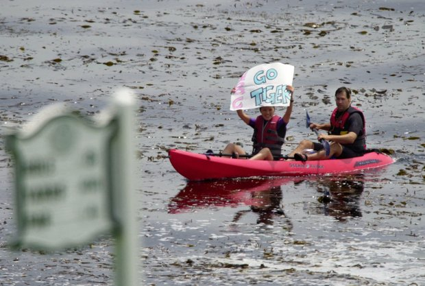 Fans in a canoe wave a sign urging on Tiger Woods during the final round of the 2000 U.S. Open.