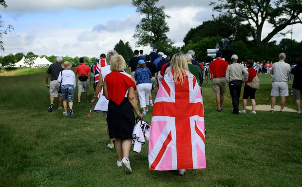 A woman walks the course wearing a Great Britain flag during the Friday morning foursomes. GB&I leads by a point.