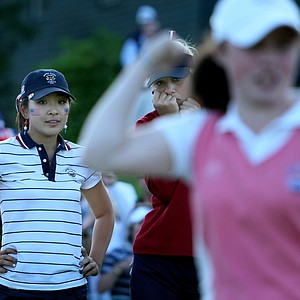 Tiffany Lua, left, and Jessica Korda watch as GB&I player Lisa Maguire sinks a putt to halve the hole at No. 18 during afternoon four-ball matches at the Curtis Cup.