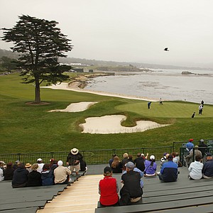 Spectators watch Monday's practice round from behind the 18th green at Pebble Beach.