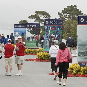 Fans walk past a tribute to the past champions at the front entrance of the U.S. Open.