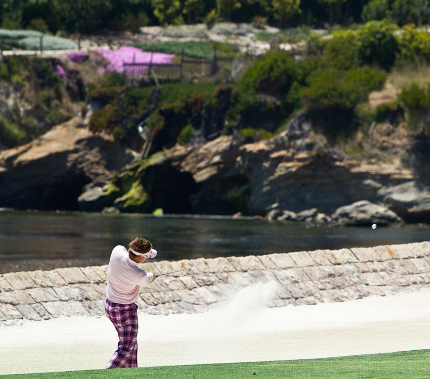 Ian Poulter plays his second shot from a bunker on the 18th hole at Pebble Beach.