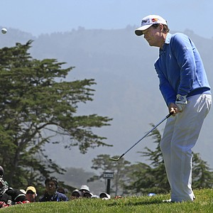 Tom Watson chips to the 12th green at Pebble Beach.