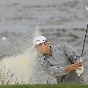 Dustin Johnson blasts out of a bunker on the eighth hole Friday at Pebble Beach.