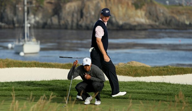 Tiger Woods lines up at putt at the 17th as Ernie Els passes behind him.