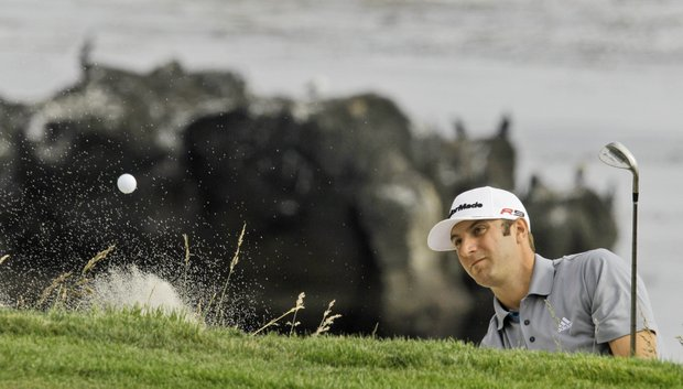 Dustin Johnson hits out of a bunker at the eighth hole.