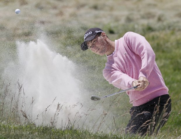 Martin Kaymer blasts out of a bunker at the first hole in Round 3.