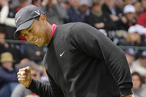 Tiger Woods celebrates after making a par-saving putt on the third hole