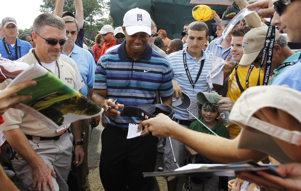 Tiger Woods signs autographs June 29 during an AT&T National practice round.