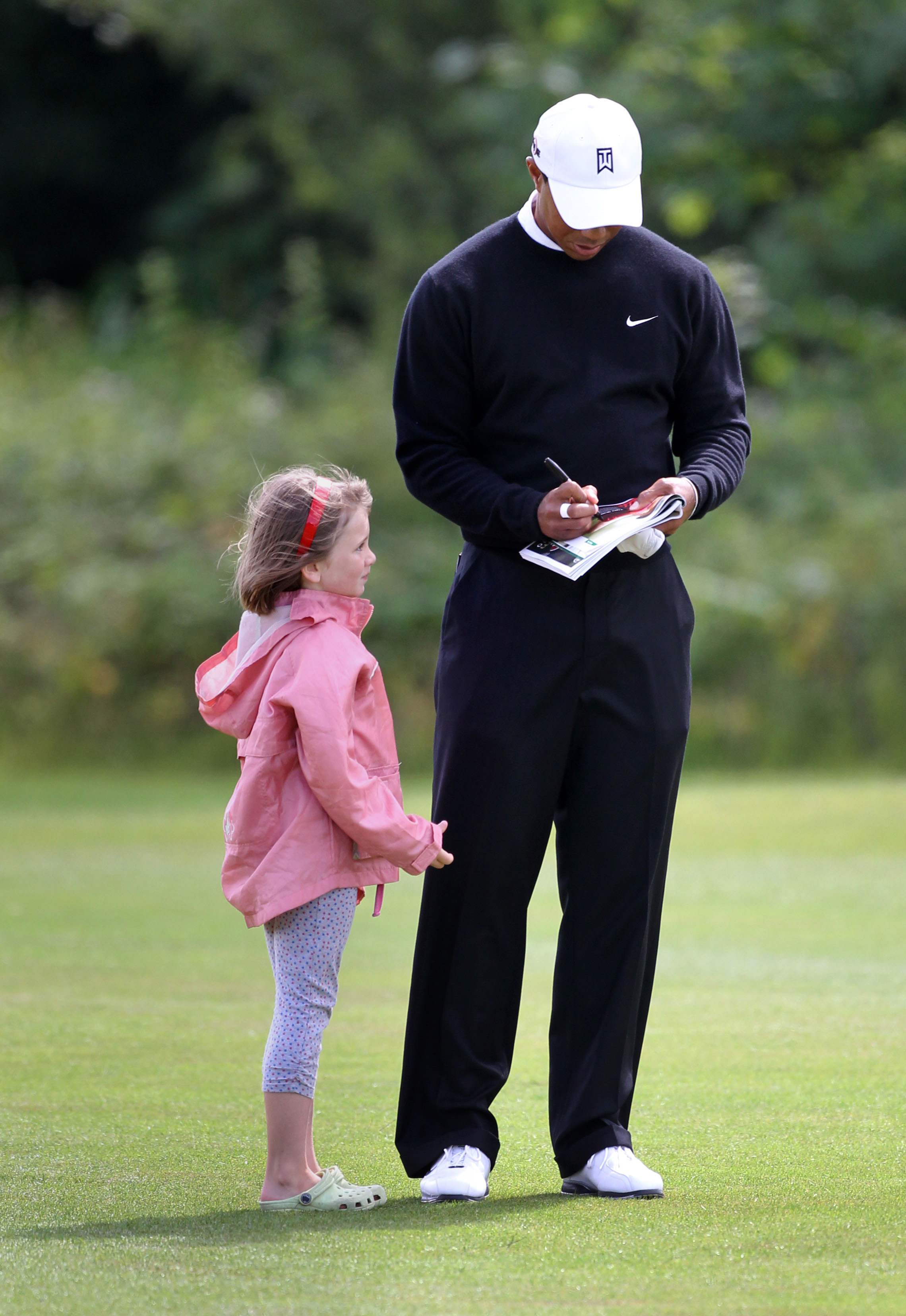 Tiger Woods signs an autograph for Ava Mulhall, 6, during the JP McManus Invitational Pro-Am.
