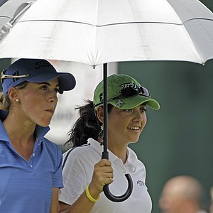 Azahara Munoz, left, and Juliana Murcia walk under an umbrella during their practice round for the U.S. Women's Open.