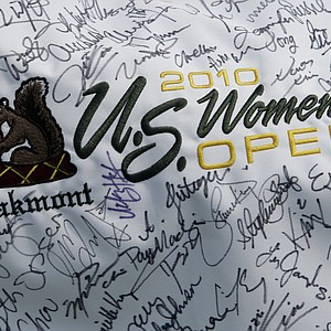 A fan holds a flag with autographs from players during a practice round for U.S. Women's Open.