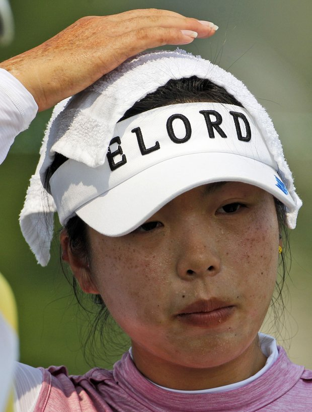 Yueer Feng places a cold cloth on her head during a practice round for the U.S. Women's Open.