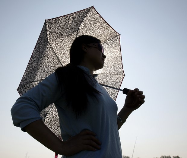 Golf fan Jame Lu takes cover under an umbrella as she watches a practice round for the U.S. Women's Open.