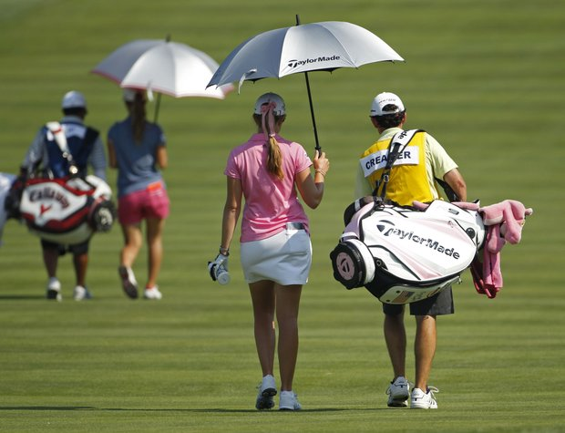 Paula Creamer, second from right, walks with her caddie down the third fairway during a practice round for the U.S. Women's Open.