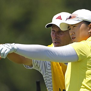 Amy Yang talks with her caddie, Greg Johnson, before teeing off on the fourth hole.