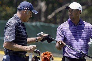 Tiger Woods gets his putter from caddy Steve Williams, during a practice round at Pebble Beach.