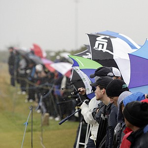 Spectators watch a British Open practice round in the rain at the Old Course at St. Andrews.
