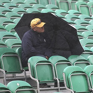 A spectator sits in the rain watching the practice rounds on the Old Course at St. Andrews.