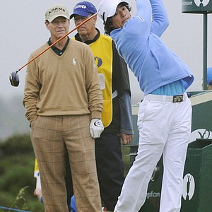 Ryo Ishikawa tees off at the sixth hole as Tom Watson looks on.