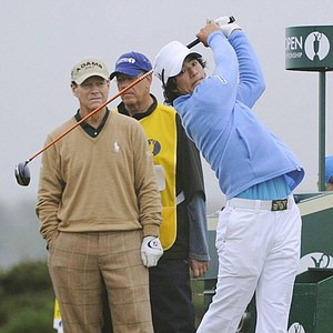 Ryo Ishikawa tees off at the sixth hole as Tom Watson looks on.