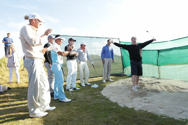 Golfweek senior writer Alistair Tait reacts after successfully hitting a ball over a net, which simulated the Road Hole Bunker on the Old Course. European Tour pros looking on include (left to right) Marcel Siem, Thongchai Jaidee, Alex Noren, Oliver Wilson, Graeme McDowell and Alvaro Quiros.