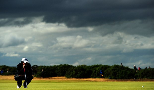 Dark clouds loom over the 9th green as Rory Mcllroy lines up a putt at the Old Course in St. Andrews.