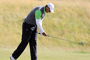 Tiger Woods slams his fairway wood into the turf after hitting an errant shot during Round 2 at the British Open.