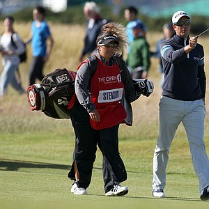 Henrik Stenson, who shot 67 in Round 3 of the British Open, walks with his caddie, Fanny Sunesson.