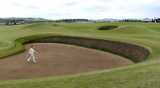 Ian Poulter walks to his ball in a bunker at the Old Course's seventh hole.